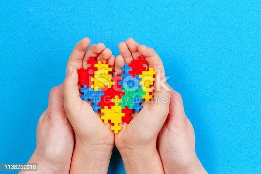 istock Adult and kid hands holding colorful heart on blue background. World autism awareness day concept 1138232616