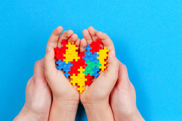 Adult and kid hands holding colorful heart on blue background. World autism awareness day concept stock photo