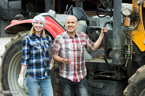 istock Adult and young farmers working at machinery 538575472