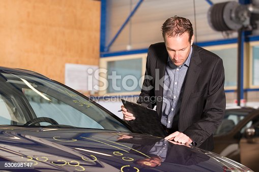 istock Adult appraiser looking at car, estimate for fix 530698147