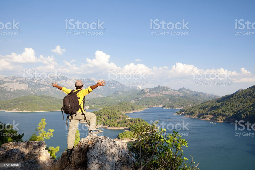 Adult backpacker man outstretched arms on the peak of mountain royalty-free stock photo