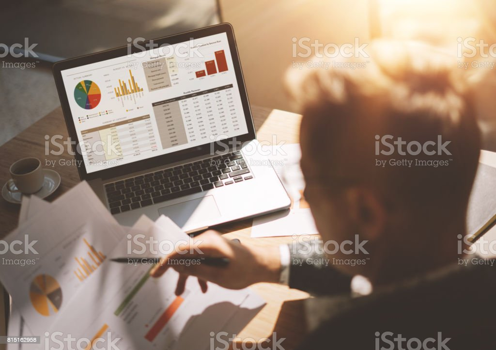 Adult banking analyst in eyeglasses working at sunny office on laptop while sitting at wooden table.Businessman analyze document in his hands.Graphs and diagramm on notebook screen.Blurred background. stock photo