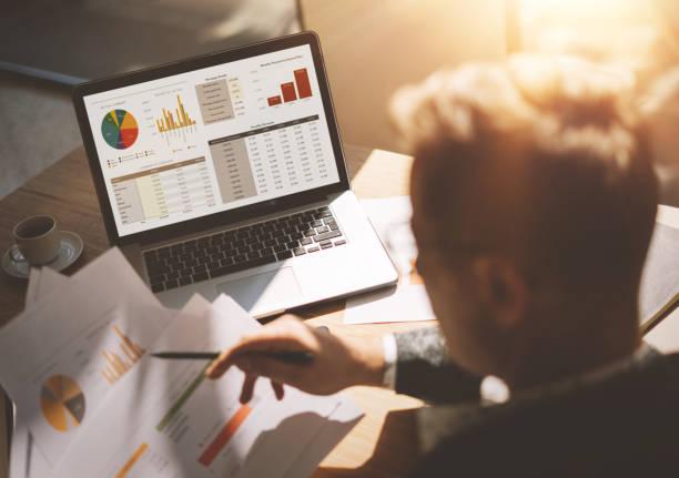Erwachsenen Banking Analyst in Brillen arbeiten bei sonnigen Büro auf Laptop beim Sitzen am Tisch aus Holz. Geschäftsmann analysieren Dokument in seinen Händen. Grafiken und Diagramm auf Notebook-Bildschirm. Der Hintergrund jedoch unscharf. – Foto