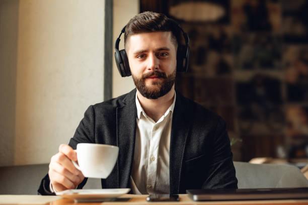 Erwachsene bärtige Mann drinnen in Café. Lifestyle-Konzeptfoto mit Kopierraum. Bild von Profi mit modernen drahtlosen schwarzen Kopfhörern und Kaffee – Foto