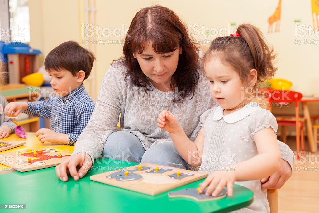 adult beautiful caucasian female teacher collect puzzle with a girl stock photo