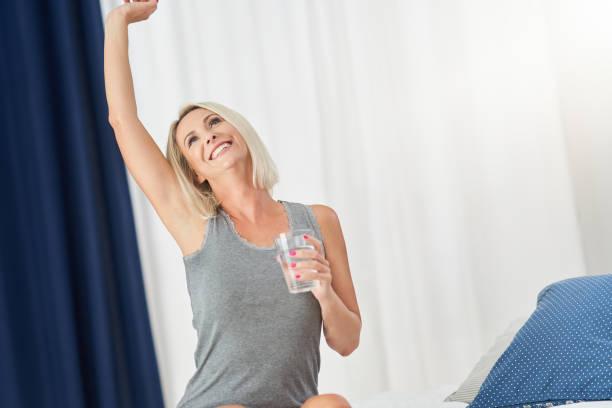 Yetişkin güzel kadın tamamen dinlenmiş ve içme suyu uyanma stok fotoğrafı
