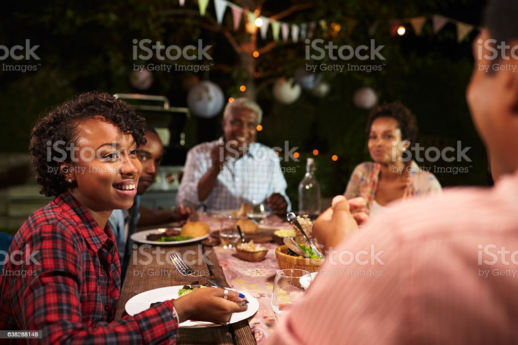 Adult black family eat dinner in garden, over shoulder view stock photo
