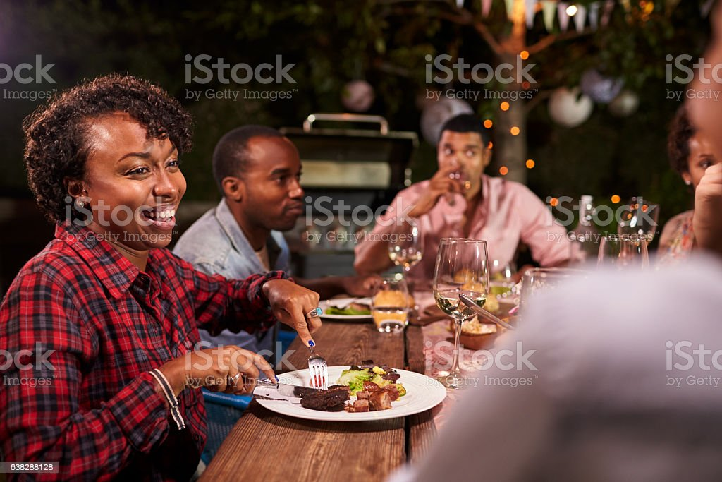 Adult black family enjoy dinner and conversation in garden stock photo