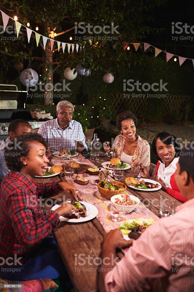 Adult black family enjoy dinner together in garden, vertical stock photo