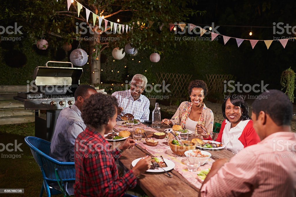 Adult black family enjoying dinner together in their garden - Photo