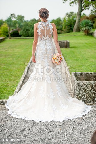 Adult Bride in Wedding Dress Looking at Park Outdoors.