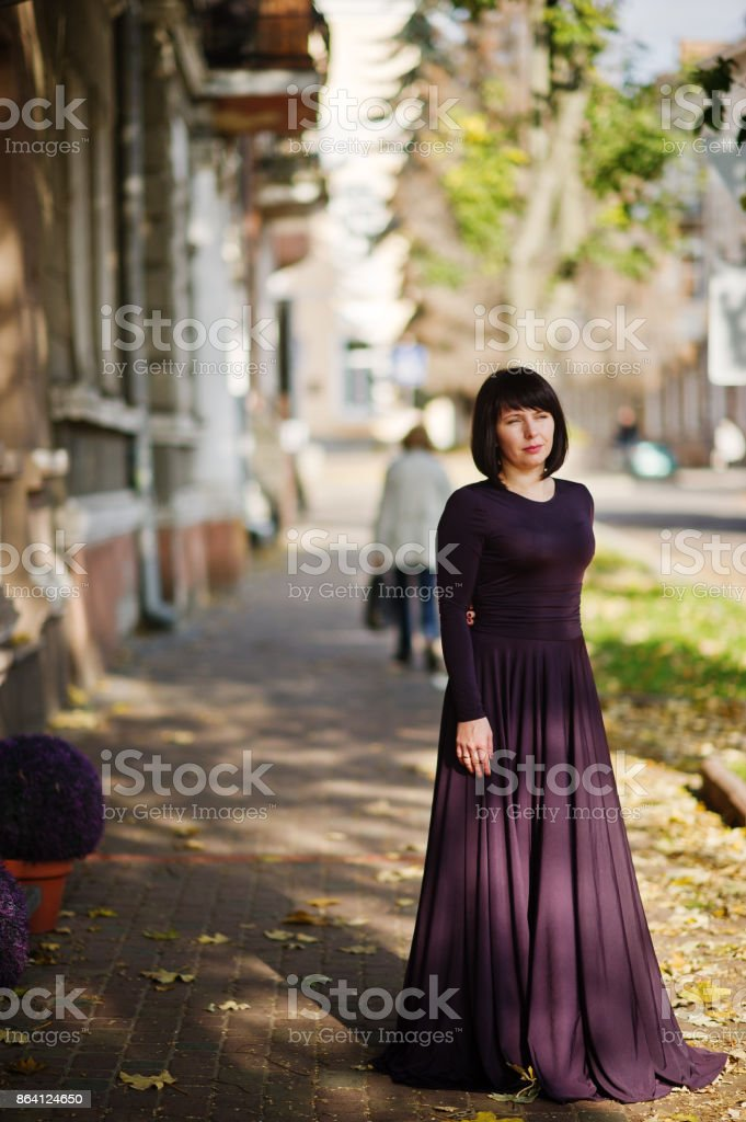 Adult brunette woman at violet gown. royalty-free stock photo