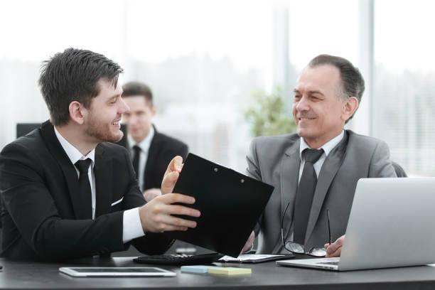 erwachsener Geschäftsmann diskutiert Finanzdokumente mit einem jungen Kollegen. – Foto
