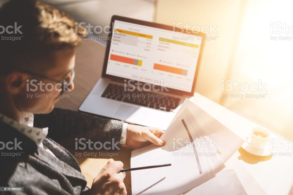 Adult businessman in eyeglasses working at sunny office on laptop while sitting at the wooden table.Man analyze document in his hands.Graphs and diagramm on notebook screen.Blurred background. stock photo