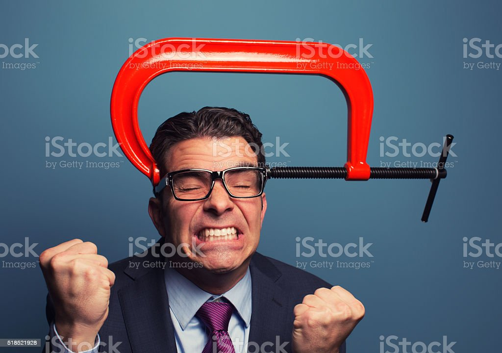 Adult Businessman In Pain with Vice on His Head stock photo