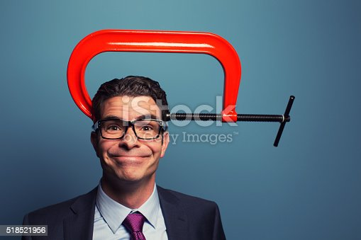A mid adult businessman dressed in suit and wearing glasses is calm under business pressure and deadlines. He has a cheesy smile on his face. The c clamp on his head has no affect on his attitude as he is happy and calm under lots of pressure.
