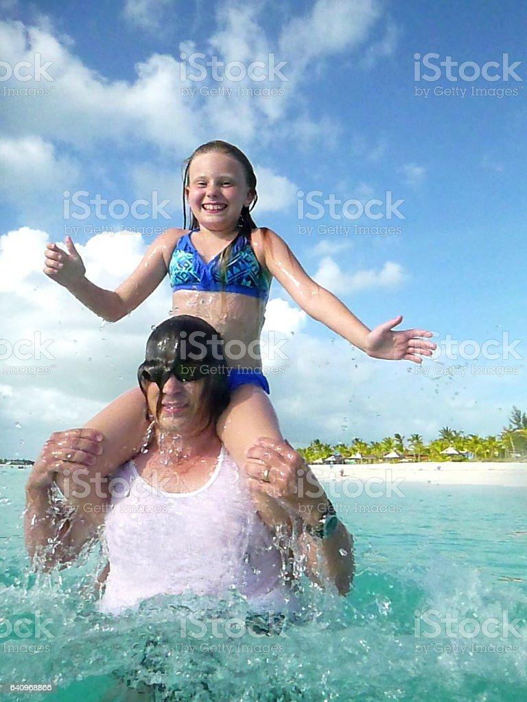 Okyanusa güneşli bir günde, Türk ve Caicos Karayip Denizi içine onun omuzlarında oturan gülen onun 10 yaşındaki kızı güneş gözlüğü, saati, beyaz tshirt ve yüzme gövdeleri, 50'li yetişkin beyaz adam atar stok fotoğrafı