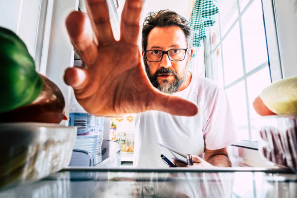Adult caucasian man take healthy food from an open fridge - closeup inside view - weight loss concept -  home activity in the kitchen - quarantine coronavirus people concept stay home stock photo