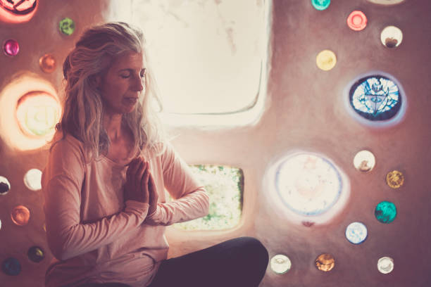 erwachsene kaukasische frau tun yoga-meditation zu hause oder unterricht mit farbigen glaswand hintergrund - konzept von wellness und gesunden lebensstil für alternative menschen - achtsamkeit persönlichkeitseigenschaft stock-fotos und bilder