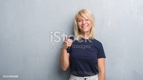 istock Adult caucasian woman over grunge grey wall happy with big smile doing ok sign, thumb up with fingers, excellent sign 1042484358