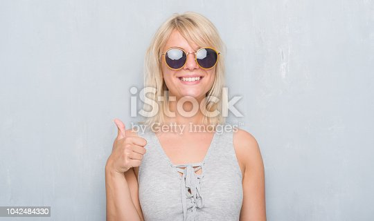 istock Adult caucasian woman over grunge grey wall wearing retro sunglasses happy with big smile doing ok sign, thumb up with fingers, excellent sign 1042484330