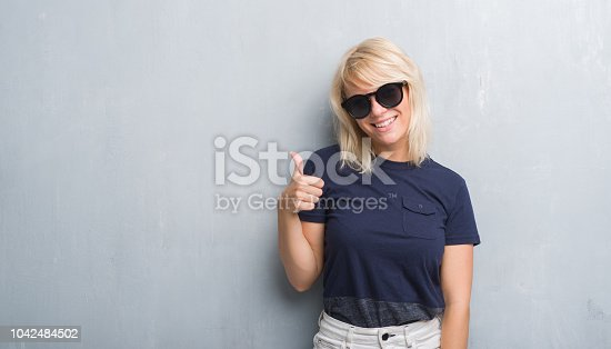 istock Adult caucasian woman over grunge grey wall wearing sunglasses doing happy thumbs up gesture with hand. Approving expression looking at the camera with showing success. 1042484502