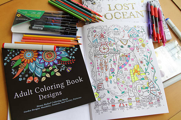 adult coloring books and variety of pencils, pens and markers - colouring book stock photos and pictures