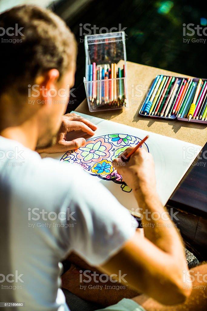 Adult colouring with soft tip pencils, designer, handsome men stock photo