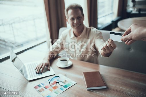 istock Adult confident man pays for lunch at restaurant. 947907966