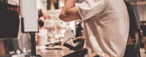 adult consumer paying with credit card in the store, holding a wallet stock photo