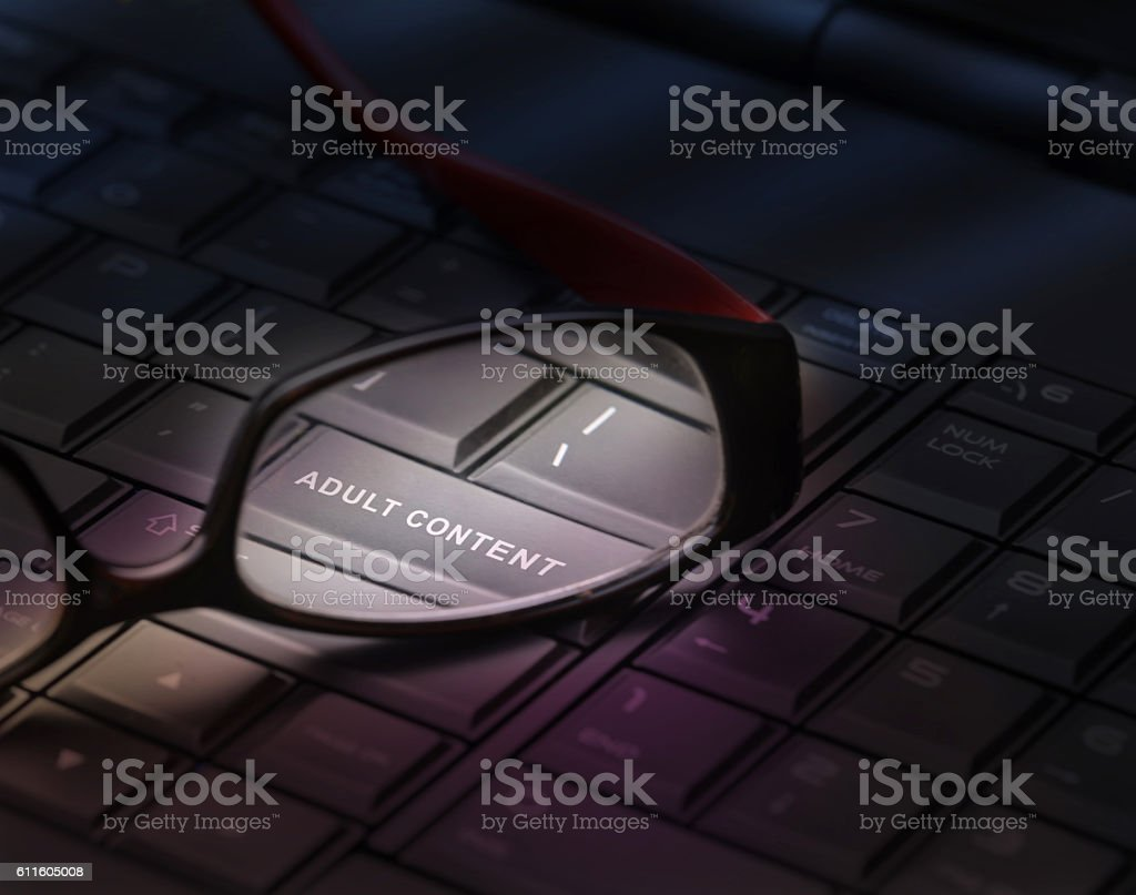 Adult content button through reading glasses. stock photo