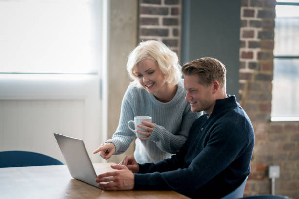 Adult couple at home and woman standing next to her partner pointing at something on the laptop's screen smiling stock photo