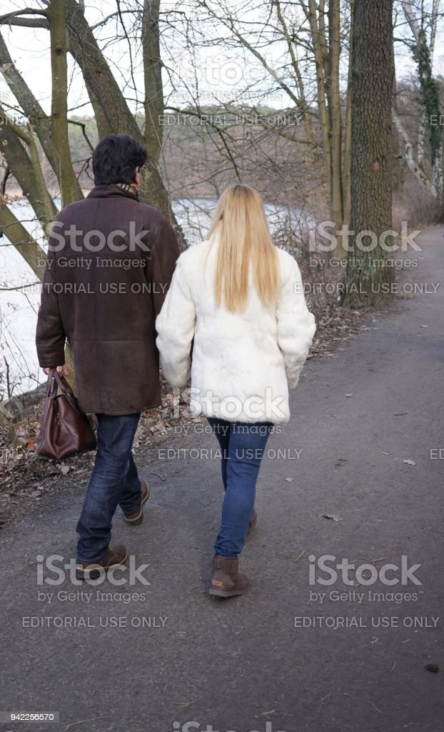 Adult couple enjoying a walkabout by the lakeshore stock photo