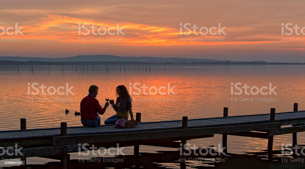 Adult couple sitting on jetty drinking wine at sunset stock photo