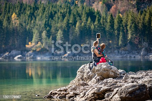 Adult Couple Taking a Selfie With Digital Tablet By a Lake.