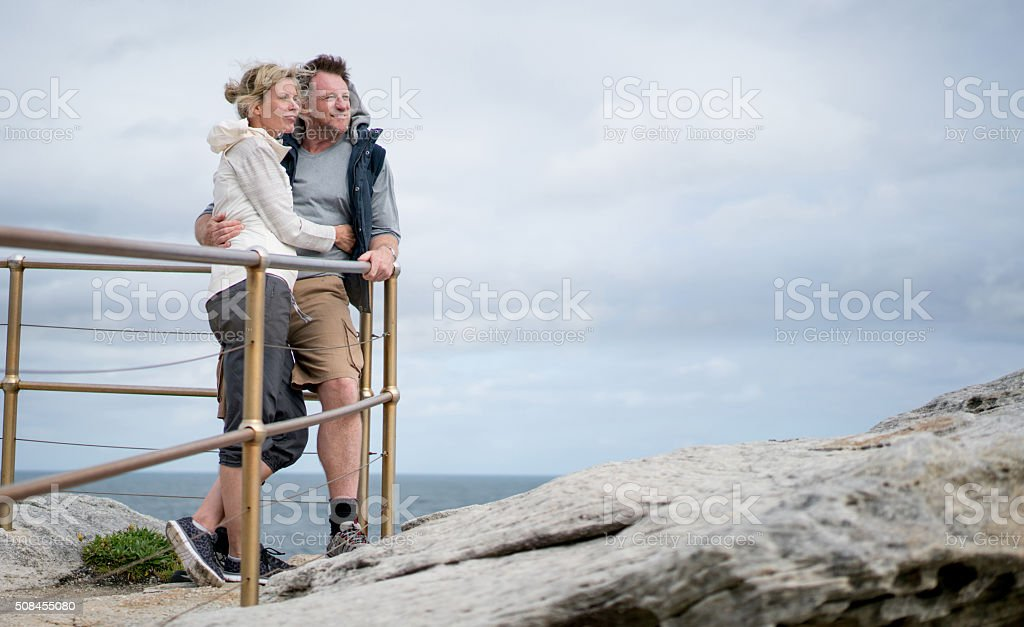 Adult couple taking a walk by the beach stock photo