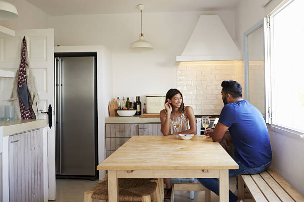 Adult couple talk and drink wine in the kitchen, copy - Photo