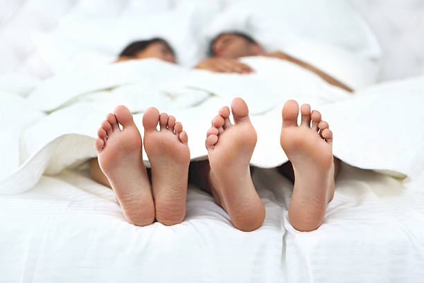 Adult couple talking in bed. Closeup of unrecognizable couple having conversation in bed. They are tucked in, but their feet  stick out of the sheet. Feet are in sharp focus. Front view. protruding stock pictures, royalty-free photos & images