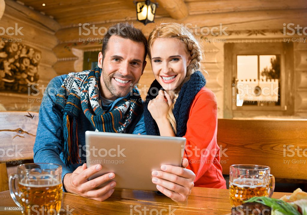 Adult couple using digital tablet Happy couple sitting in a mountain restaurant after skiing, enjoying beer and using a digital tablet, smiling at the camera. Adult Stock Photo