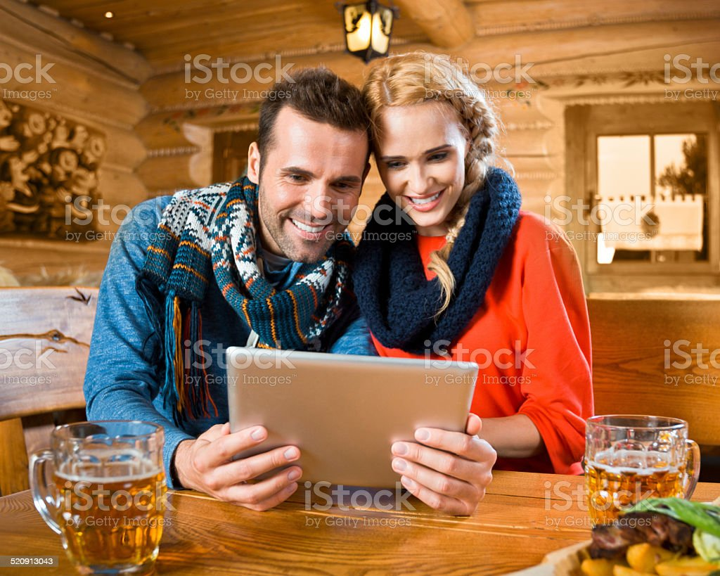 Adult couple using digital tablet Happy couple sitting in a mountain restaurant after skiing, enjoying beer and using a digital tablet.  Adult Stock Photo