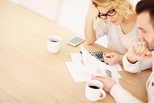 adult couple working on documents - mortgages and loans stock pictures, royalty-free photos & images