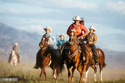 516318379 istock photo Adult cowgirls riding galloping horses 1134191227