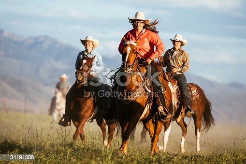 516318379 istock photo Adult cowgirls riding galloping horses 1134191308