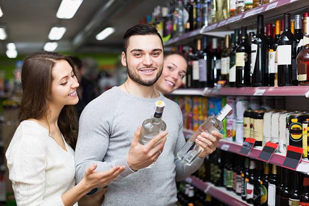 adulte les clients choisissant de vodka - spiritueux photos et images de collection