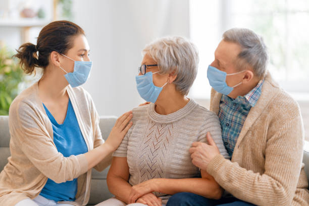 Adult daughter and senior parents wearing facemasks stock photo