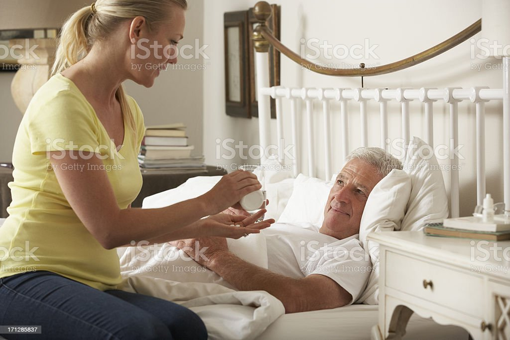 Adult Daughter Giving Senior Male Parent Medication In Bed royalty-free stock photo