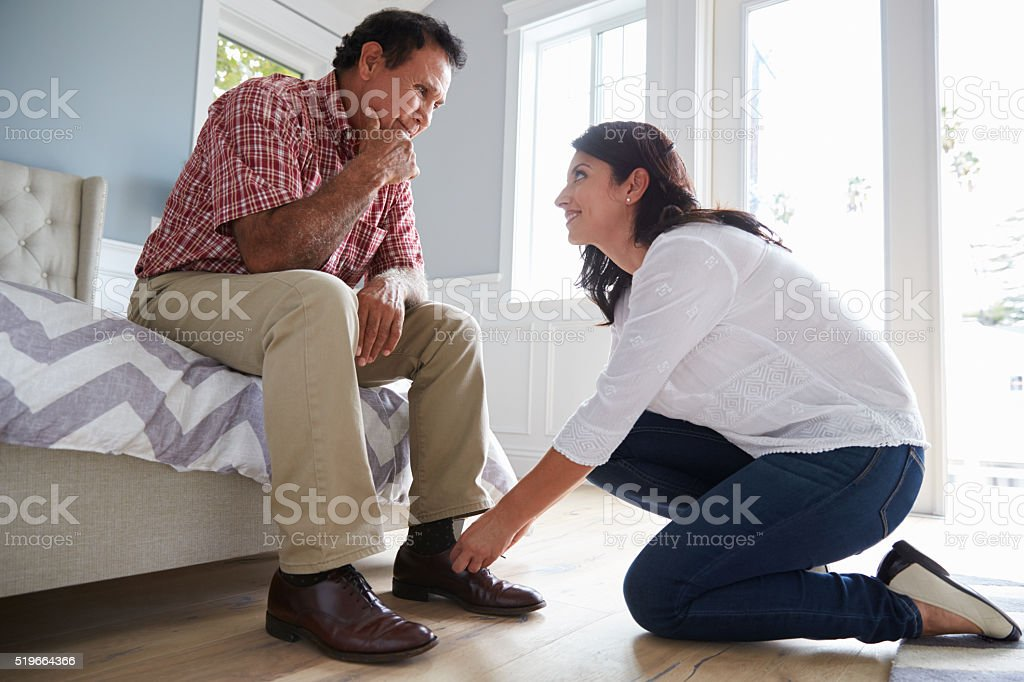 Adult Daughter Helps Father Suffering With Dementia To Dress stock photo