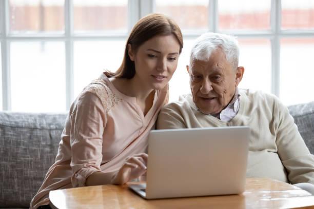 dorosła córka starego ojca wybiera usługi za pośrednictwem internetu za pomocą komputera - dojrzały zdjęcia i obrazy z banku zdjęć