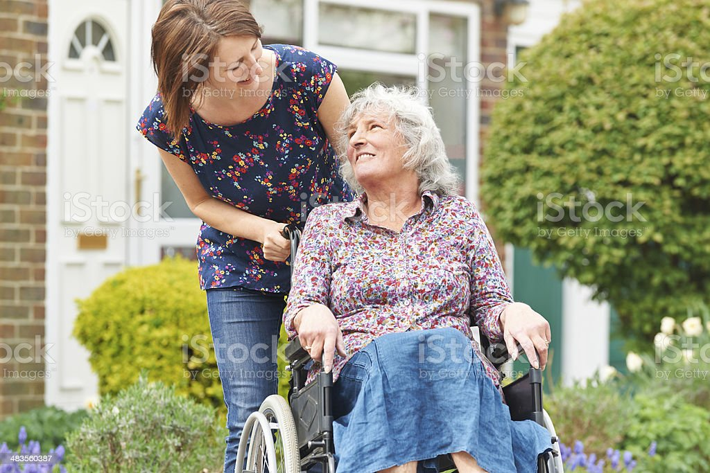 Adult Daughter Pushing Mother In Wheelchair royalty-free stock photo
