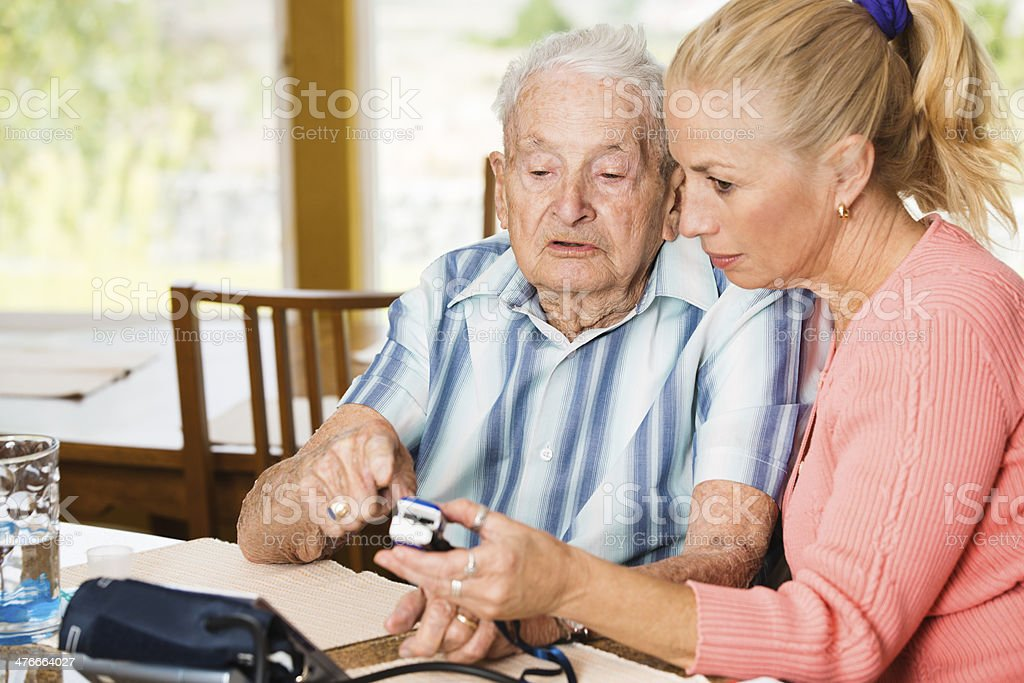 Adult daughter taking her senior father oxygen level readings royalty-free stock photo